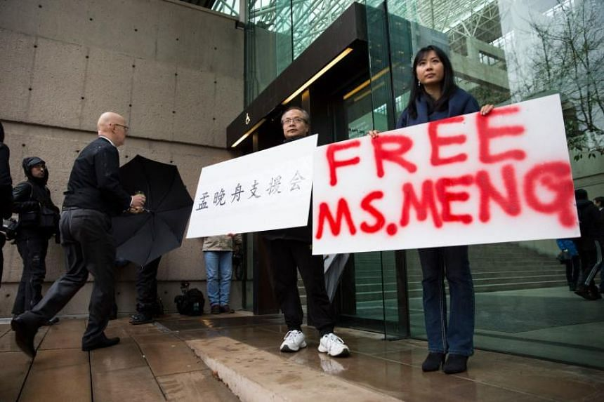 People hold signs in favour of Huawei Technologies chief financial officer Meng Wanzhou outside her bail hearing at British Columbia Superior Courts in Vancouver, on Dec 11, 2018.