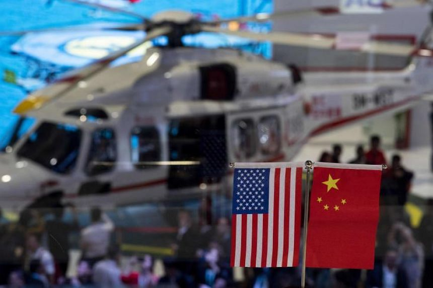 A Chinese and US flag at a booth during the first China International Import Expo in Shanghai, on Nov 6, 2018.