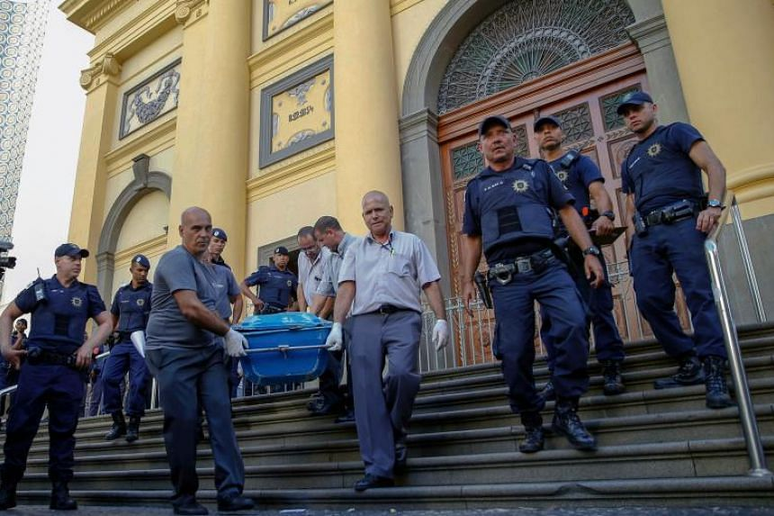 Municipal workers carry a corpse from the Cathedral of Campinas, 90km northwest of Sao Paulo, Brazil, after a man opened fire during mass and killed at least five people before committing suicide, on Dec 11, 2018.