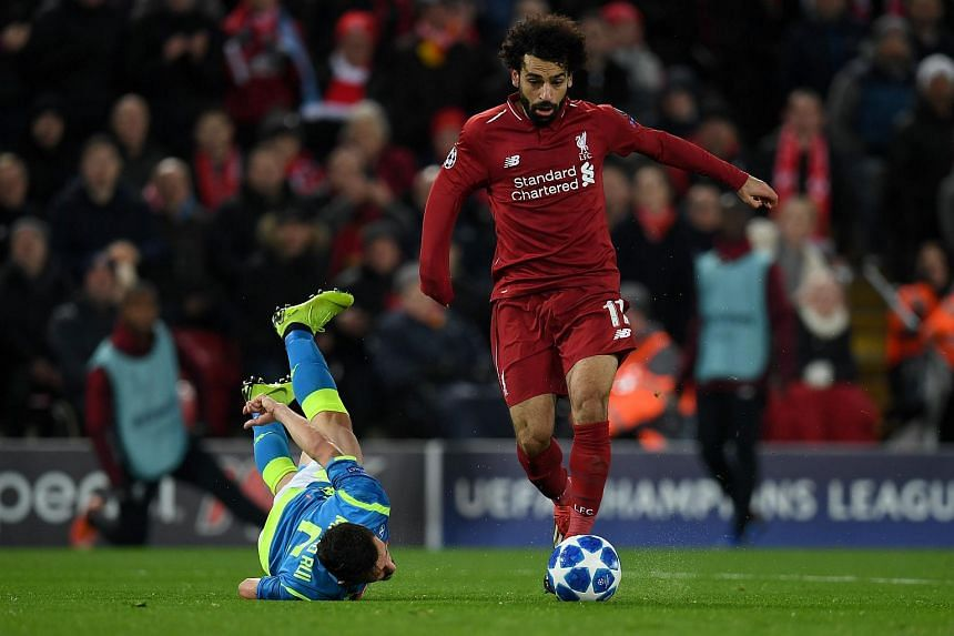Liverpool's Egyptian midfielder Mohamed Salah (right) runs past Napoli's Portuguese defender Mario Rui during the UEFA Champions League group C football match between Liverpool and Napoli at Anfield stadium in Liverpool, north west England, on Dec 11