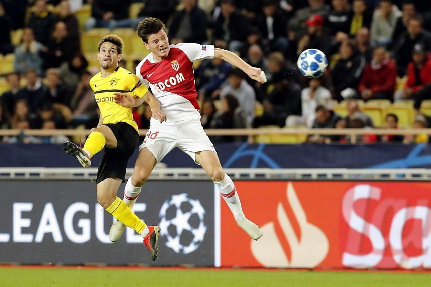 Raphael Guerreiro of Borussia Dortmund (left) in action against Giulian Biancone of AS Monaco during the UEFA Champions League Group A match at Stade Louis II, in Monaco, on Dec 11, 2018.