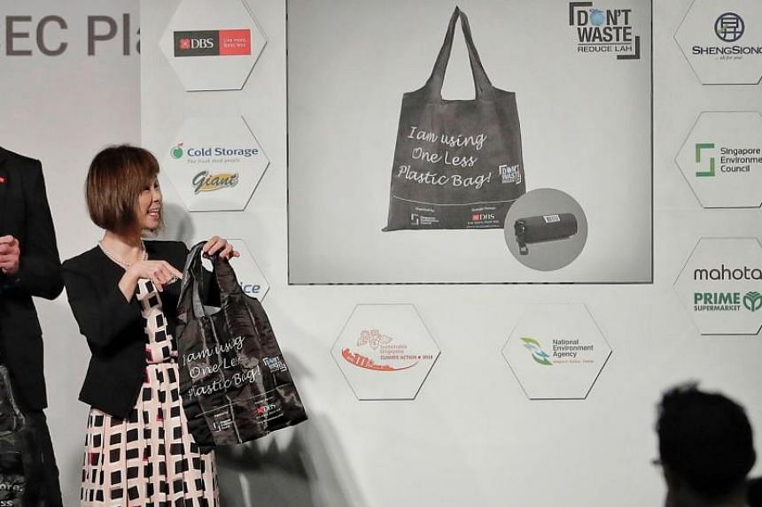 Dr Amy Khor, Senior Minister of State for the Environment and Water Resources, holding the One Less Plastic reusable bag which carries a barcode that tracks usage and behaviour of shoppers, during its launch on Dec 12, 2018.