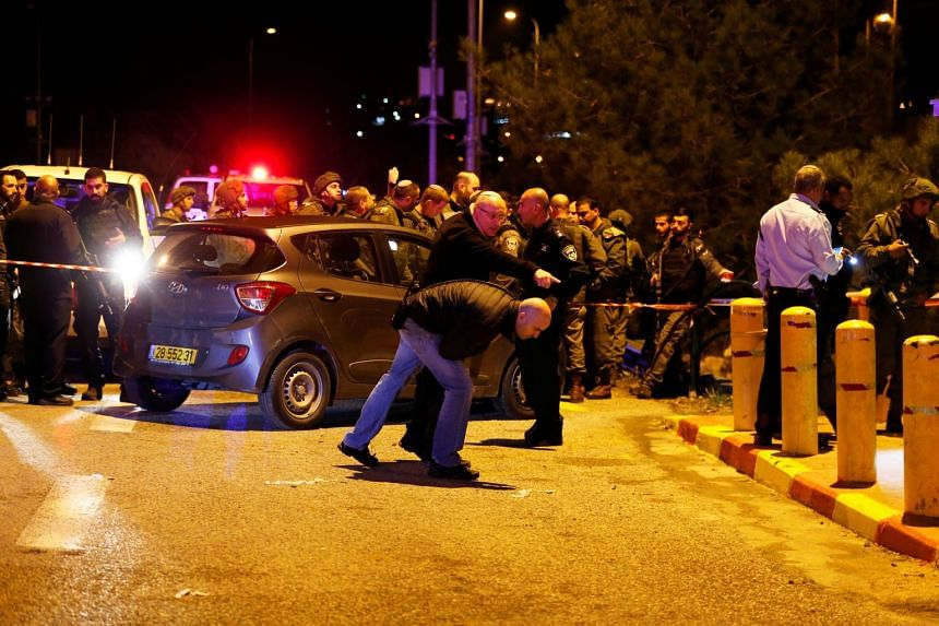 Israeli security forces and emergency personnel work at the scene after the shooting attack.