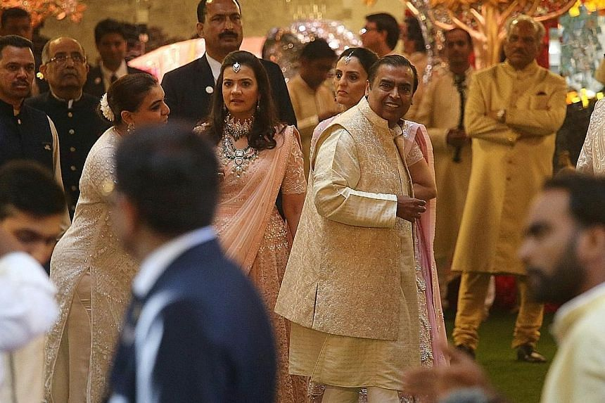 Above: The wedding procession outside the Ambanis' 27-storey home. Ms Isha Ambani married Mr Anand Piramal, the scion of another wealthy family. Above: Mr Mukesh Ambani, chairman of oil-to-telecoms conglomerate Reliance Industries, at his only daught