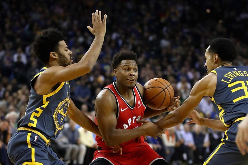 Kyle Lowry is guarded by Quinn Cook and Shaun Livingston at Oracle Arena on Dec 12, 2018 in Oakland, California.