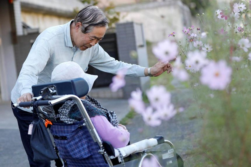 Mr Eiichi Okubo, 71, speaks to his wife Yumiko, 68, who has been suffering from dementia, near her care house in Tokyo, Japan, on Oct 29, 2018.