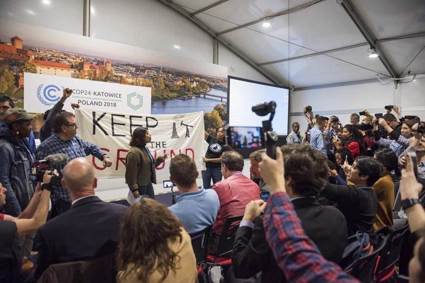 Protesters disrupt a panel discussion on fossil fuels hosted by US President Donald Trump's international energy and climate adviser Wells Griffith at the United Nations Framework Convention on Climate Change in Katowice, Poland, on Dec 10, 2018.