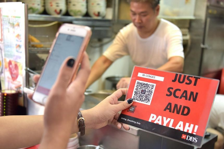 A patron paying for her food using the DBS PayLah mobile payment app at a hawker centre in Toa Payoh, on Sept 6, 2017.