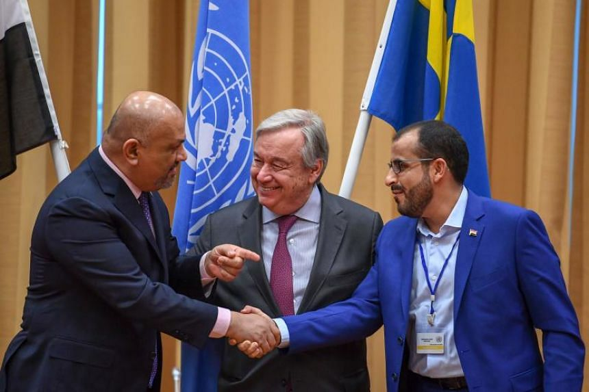 Yemen's Foreign Minister Khaled al-Yamani (left) and rebel negotiator Mohammed Abdelsalam shaking hands as United Nations chief Antonio Guterres looks on, during peace consultations at Johannesberg Castle in Rimbo, Sweden, on Dec 13, 2018.