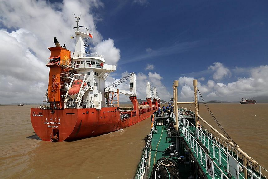 A Sinopec oil tanker approaching cargo vessel Dongtai Baoze (left) berthed at an anchorage off Zhoushan port to supply it with bunker fuel on Aug 14. Zhoushan was ranked fourth in global container traffic in 2016, according to the World Shipping Coun