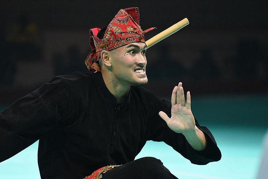 Iqbal Abdul Rahman showing his skills in the men's artistic single event at the 18th World Pencak Silat Championship yesterday. The 25-year-old Singaporean clinched his first world title in five attempts.