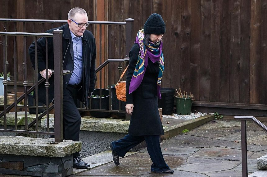 Huawei's chief financial officer Meng Wanzhou leaving her home under the supervision of security in the Canadian city of Vancouver on Wednesday. She faces an 11pm to 7am curfew while on bail.