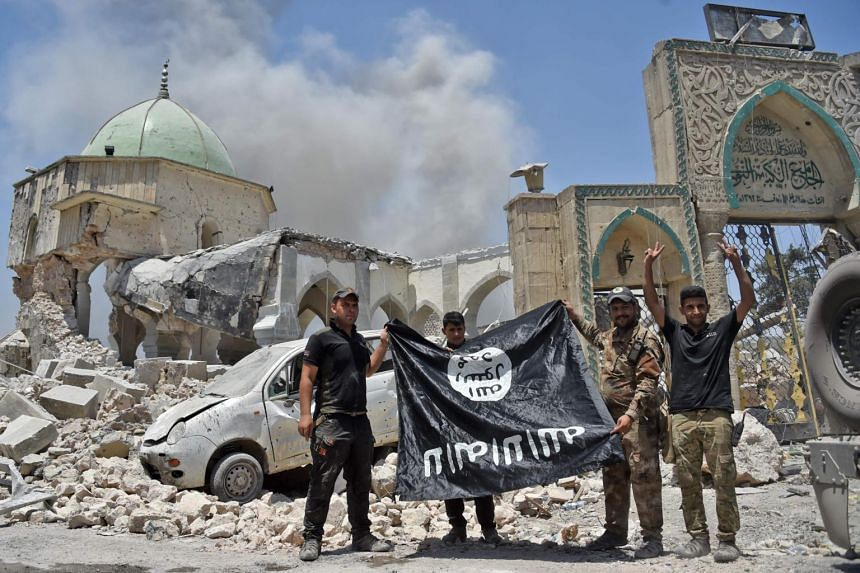 File photo of members of the Iraqi Counter-Terrorism Service with a flag of the Islamic State held upside down, outside the destroyed Al-Nuri Mosque in the Old City of Mosul, after the area was retaken from ISIS.