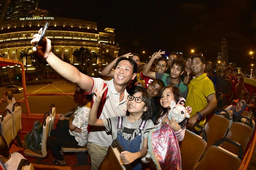 MP Louis Ng takes a wefie with foreign workers, children from low-income families and staff from Nee Soon Town Council during a bus tour to Orchard Road and the City Hall area on Dec 13, 2018.