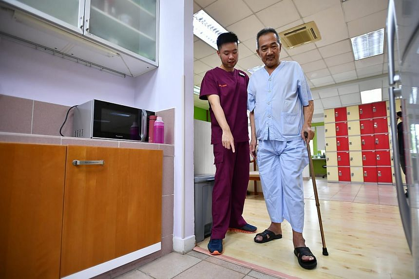 Mr Max Lim, 28, Senior Occupational Therapist, trains Mr Cheng Yam Kwang, 66, to perform daily activities in a simulated home environment at Rehabilitation Centre of Alexandra Hospital on Dec 14, 2018.