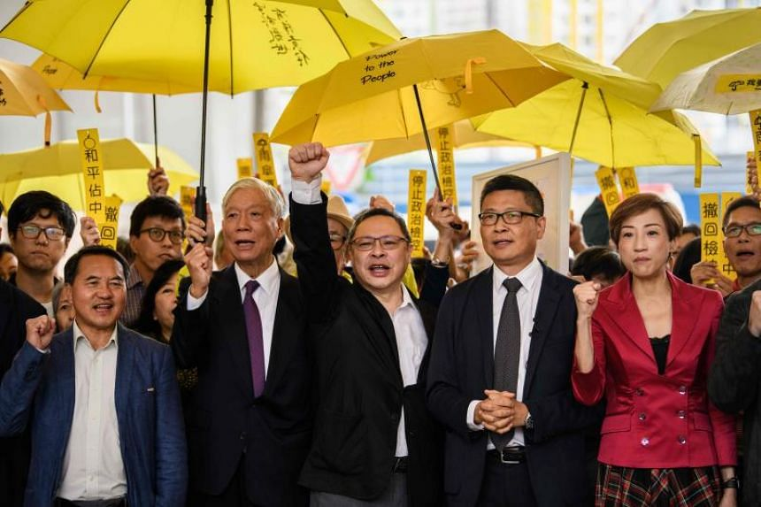 Hong Kong pro-democracy campaigners including retired pastor Chu Yiu Ming (second from left), law professor Benny Tai (centre) and retired sociologist Chan Kin Man (second from right) chant before entering the West Kowloon Magistrates Court in Hong K