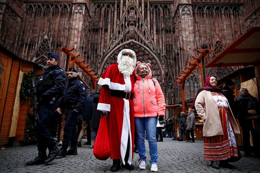 French police patrol outside Strasbourg Cathedral as a man dressed as Father Christmas poses with a tourist.