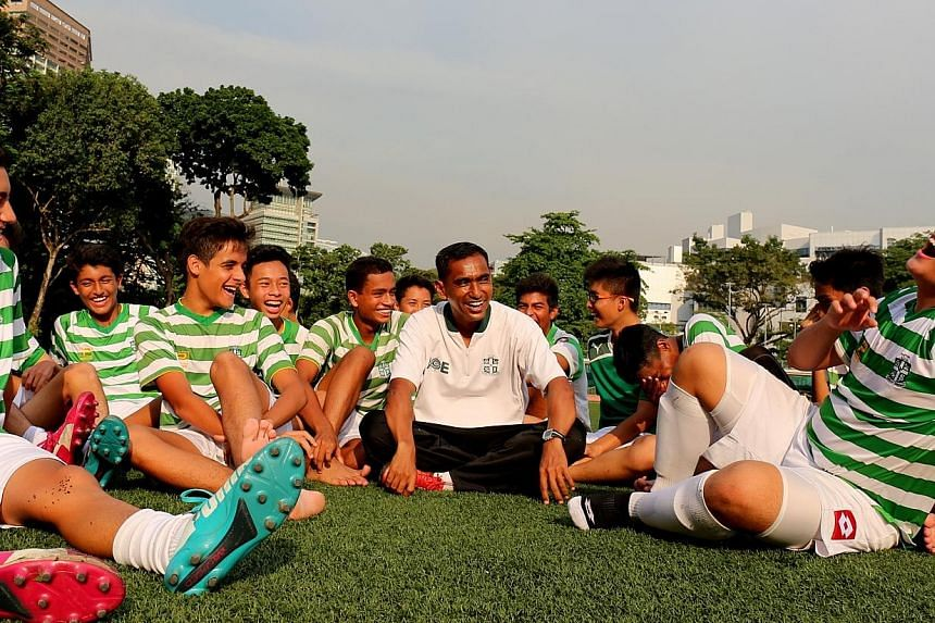 Kadir Yahaya with some young players from St Joseph's Institution. The new Tampines Rovers adviser, who coached SJI's C Division team to the schools south zone title for the past two years, remains contracted to SJI.
