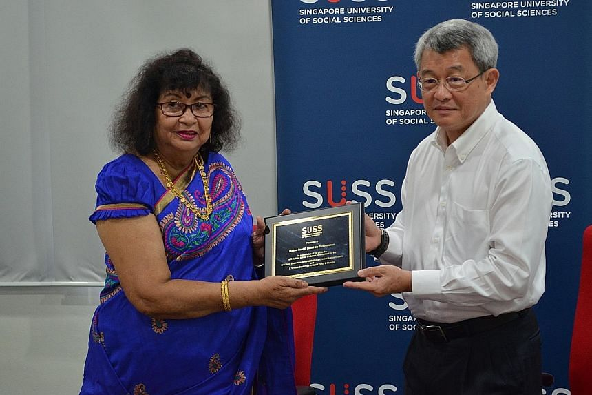 Singapore University of Social Sciences (SUSS) provost Tsui Kai Chong presenting a token of appreciation to Mr K.V. Veloo's wife Rani.