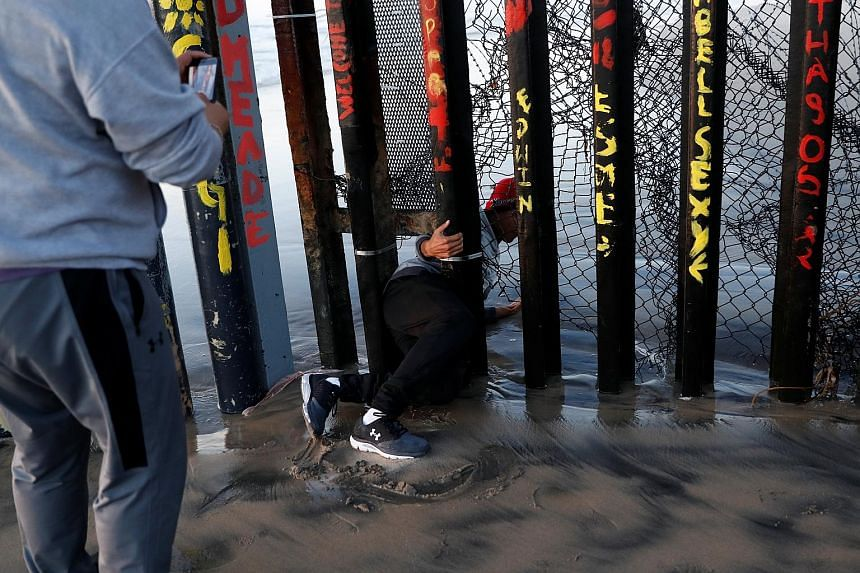 A migrant, who was part of a caravan of thousands from Central America trying to reach the United States, crawling through a gap in the border wall to cross illegally from Mexico's Tijuana to the US on Thursday. On the same day, The Washington Post r