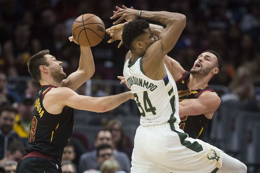 Milwaukee Bucks' Giannis Antetokounmpo (centre) tries to drive between Cleveland Cavaliers' Matthew Dellavedova (left) and Larry Nance Jr. (right) at Quicken Loans Arena, Cleveland, on Dec 15, 2018.
