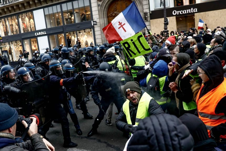 Teargas was fired at small groups of protesters in brief clashes with riot police near the Champs-Elysees.