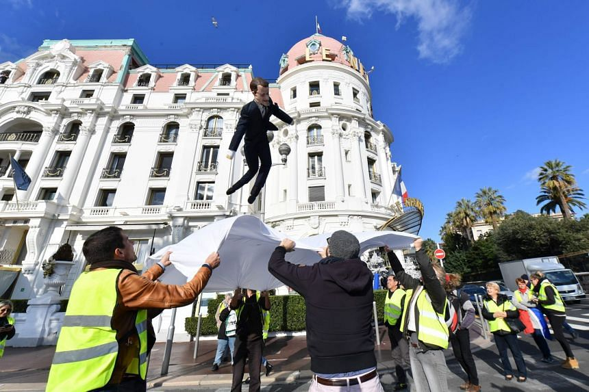 Protesters throw an effigy of French President Emanuel Macron into a sheet, a local carnival tradition, in Nice, France, on Dec 15, 2018.