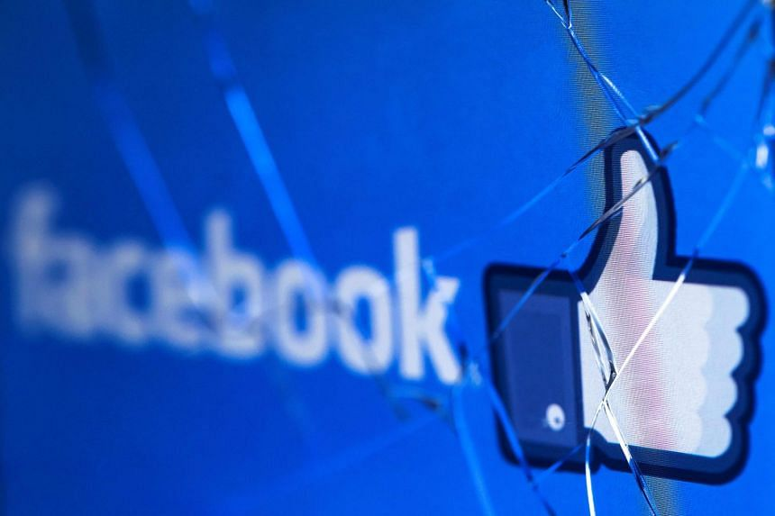 Facebook's logo is seen on the broken screen of a mobile phone.