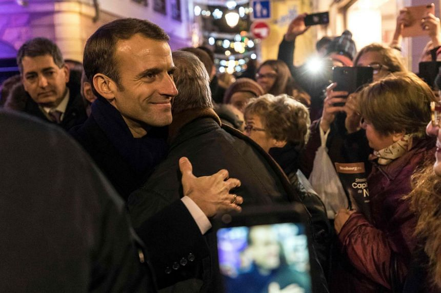 Macron hugs a man as he visits the Christmas market in Strasbourg on Dec 14, 2018.