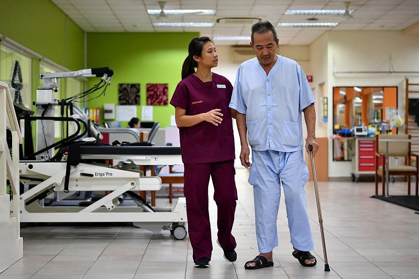 Physiotherapist Chua Xing Jun, 26, walking with Mr Cheng Yam Kwang, 66, in a simulated home environment at Rehabilitation Centre of Alexandra Hospital, on Dec 14, 2018.