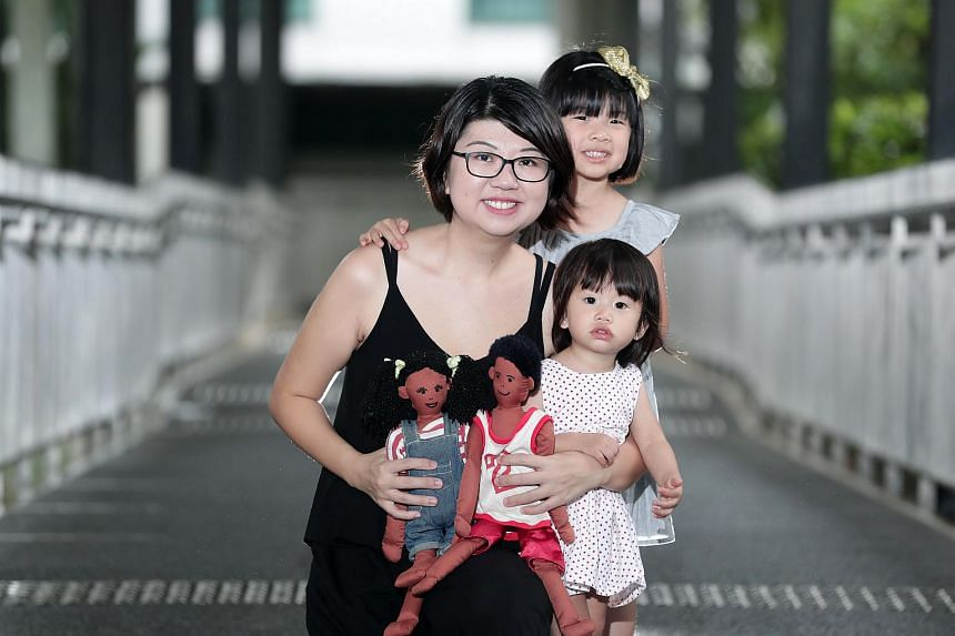 Ms Jinny Koh with her two daughters, Ariel and Esther. Ms Koh is  holding the dolls she received from her former domestic helper, Elizabeth.