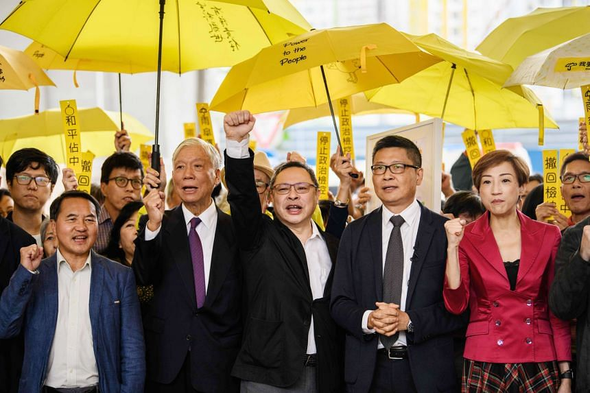 Pro-democracry activists, including (from second from left) Baptist minister Chu Yiu Ming, 74, law professor Benny Tai and sociology professor Chan Kin Man, 59, chanting before entering a Hong Kong court last month. Nine defendants face up to seven years