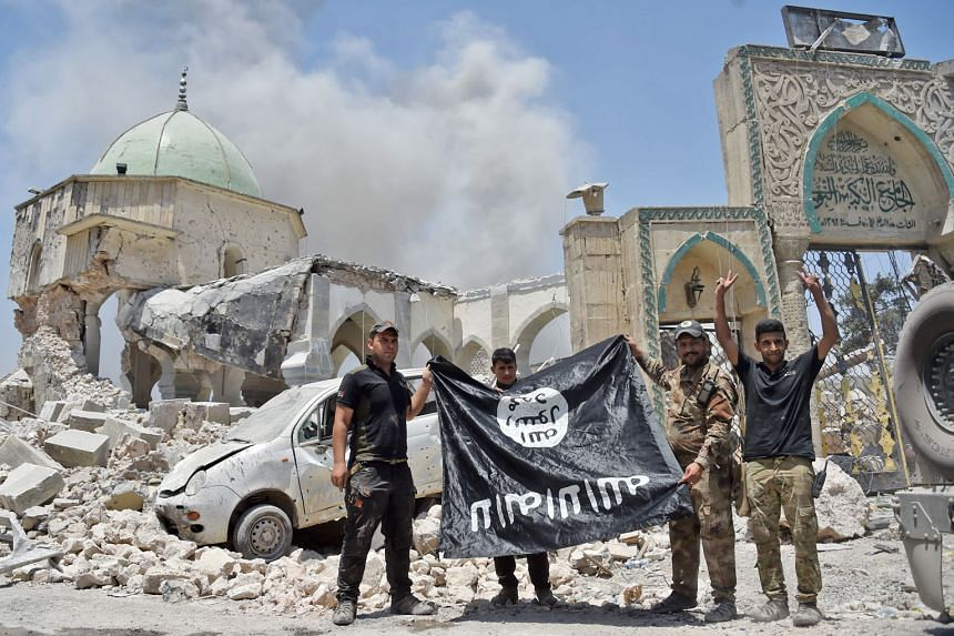 """Iraqi soldiers posing for a photo with the ISIS flag turned upside down after they retook Mosul from ISIS in June last year. Experts say that ISIS was prepared to cede the territory it once held in its self-styled """"caliphate"""" and has switched to a mo"""