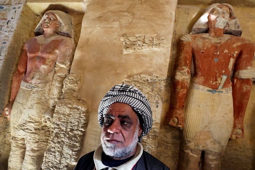 An Egyptian archaeological worker stands inside the newly-discovered tomb of Wahtye, which dates from the rule of King Neferirkare Kakai.