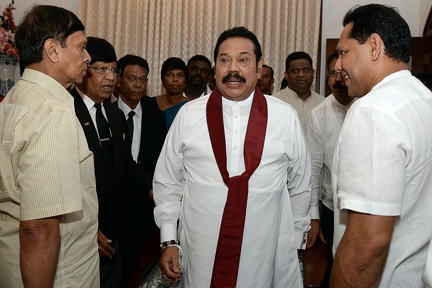 Mr Mahinda Rajapaksa with supporters yesterday after backing down from the premier's post that was controversially conferred on him.