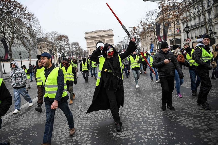 People in yellow vests marching yesterday near the Arc de Triomphe in Paris, to protest against President Emmanuel Macron's economic policies. Tear gas was fired at small groups of protesters in brief clashes with riot police near the Champs-Elysees,