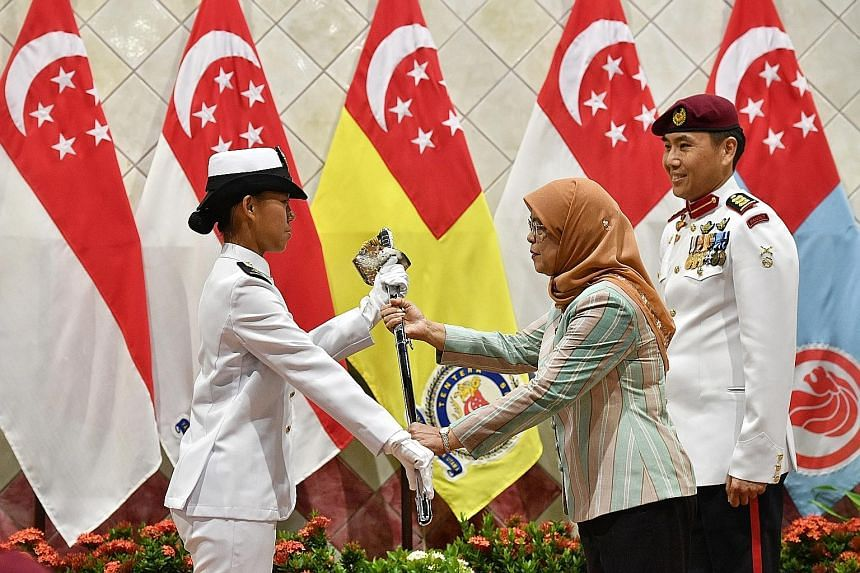 Left: Officer cadets braving the rain during the officer commissioning parade at Safti Military Institute yesterday. Right: Second-Lieutenant Audrey Tey Ee Teng, 19, receiving the sword of honour from President Halimah Yacob. The intake of 384 cadets