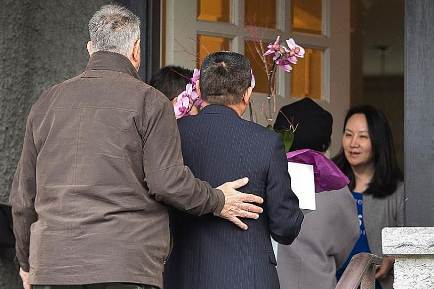 Ms Meng Wanzhou (right in picture), greeting people delivering flowers to her home in Vancouver last Wednesday after she was released on bail. She lives in Shenzhen, but also has two homes in Canada and a duplex in Hong Kong.