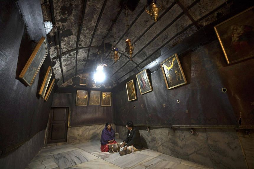 Christian pilgrims pray at the Grotto in the Church of Nativity in the West Bank city of Bethlehem, on Dec 12, 2018.