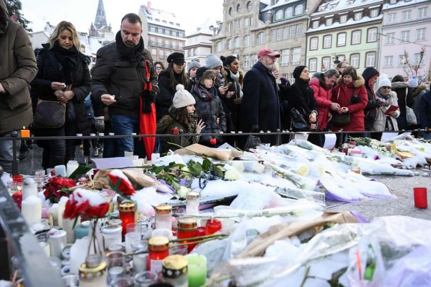 People lighting candles and leaving flowers at a makeshift memorial at Place Kleber in Strasbourg to pay tribute to the victims of the attack, on Dec 16, 2018.