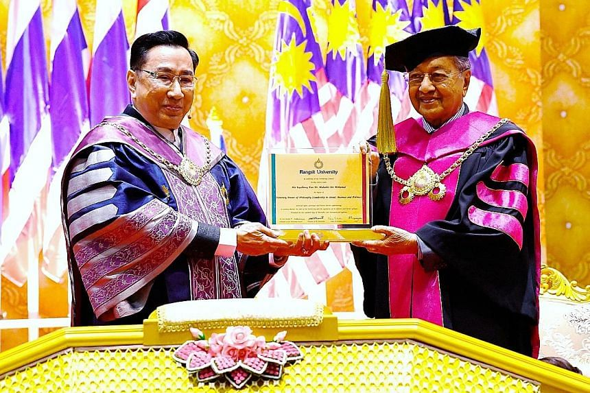 Malaysian Prime Minister Mahathir Mohamad receiving an honorary doctorate degree in social leadership, entrepreneurship and politics yesterday from Dr Arthit Ou Rairat (far left), president of Thailand's Rangsit University.