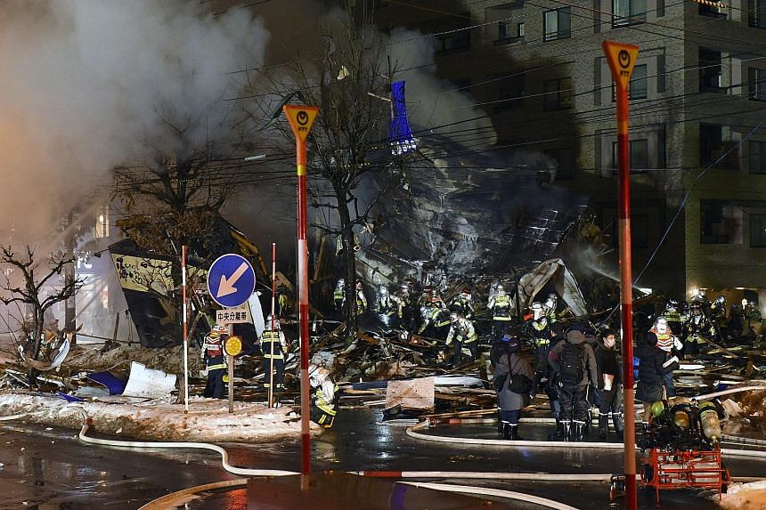 Firefighters putting out a blaze at the site of a restaurant that was razed by an explosion in Sapporo, northern Japan, yesterday. At least 42 people were injured in the blast at the two-storey Umi Sakura izakaya bar in Hiragishi district. One of the