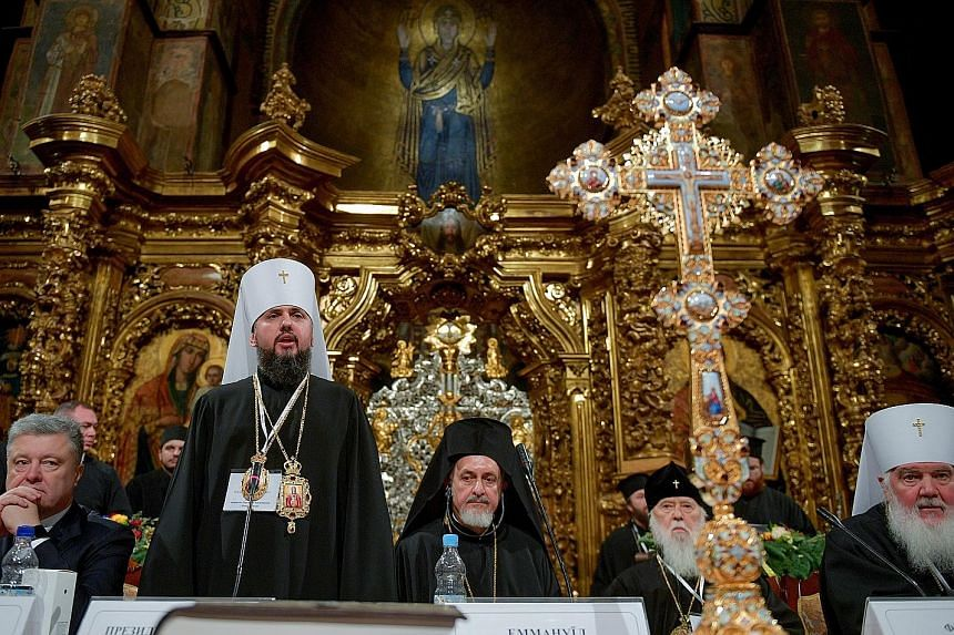 Metropolitan Epifaniy (standing), elected as leader of Ukraine's newly independent Church, speaking at the St Sophia Cathedral in Kiev, Ukraine, last Saturday. Also present was Ukrainian President Petro Poroshenko (left).