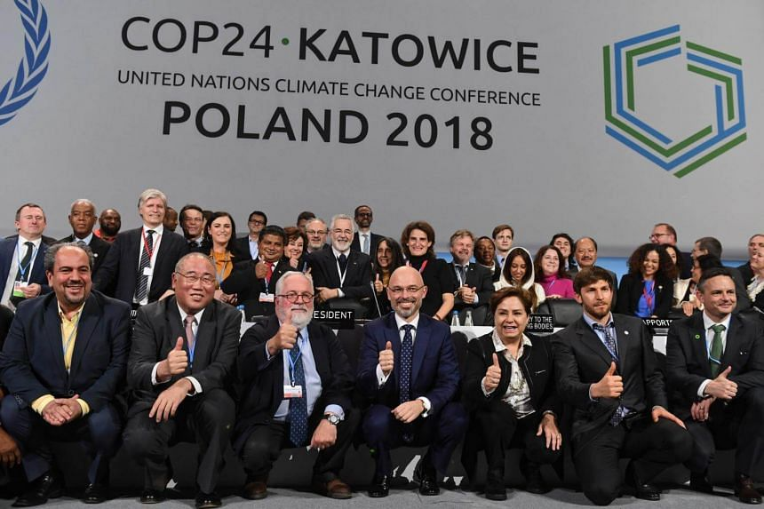 Michal Kurtyka (fourth from left), president of the United Nations climate talks and State Secretary of Poland's Ministry of Energy, and other officials posing for a photo following discussions on climate change.