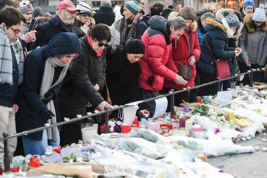 People light up candles and deposit flowers during a gathering around a makeshift memorial at Place Kleber, in Strasbourg, on Dec 16, 2018, to pay a tribute to the victims of Strasbourg's attack.