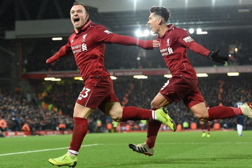 Liverpool's Swiss midfielder Xherdan Shaqiri celebrates with Liverpool's Brazilian midfielder Roberto Firmino (right) after scoring their third goal during the EPL match between Liverpool and Manchester United at Anfield in Liverpool, north west Engl