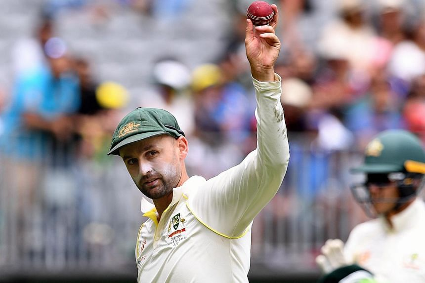 Australian bowler Nathan Lyon shows the ball after taking five wickets on day three of the second Test match between Australia and India at Perth Stadium in Perth, Australia, on Dec 16, 2018.