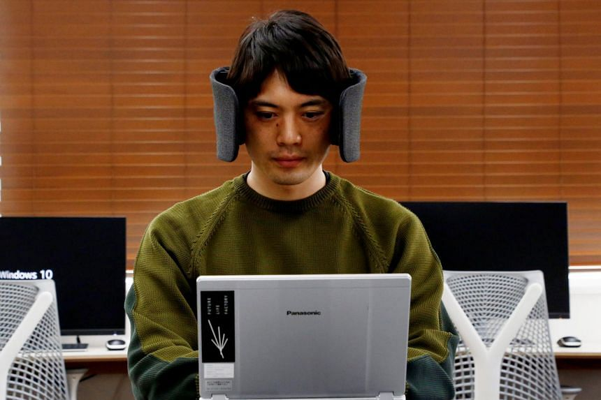 "A Panasonic designer demonstrates a prototype of the ""Wear Space"" headset, which limits noise and peripheral vision."
