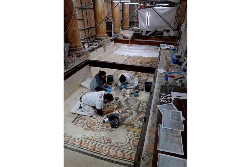 Italian artists cleaning and restoring pebble mosaics at the church's nave last month.