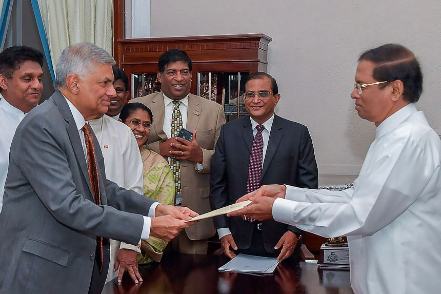President Maithripala Sirisena (right) handing over documents to reappointed Prime Minister Ranil Wickremesinghe.